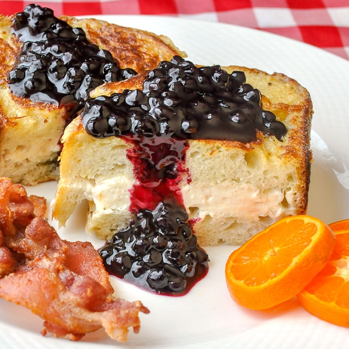 Cream Cheese Stuffed French Toast with Blueberry Sauce shown with bacon and orange slices on a white plate
