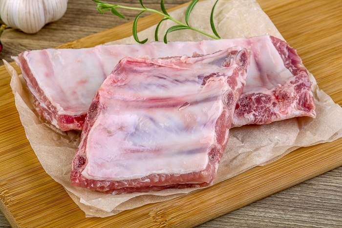 Uncooked pork ribs on a wooden cutting board