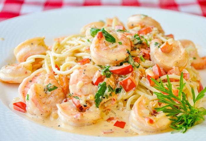 Spicy Creamy Garlic Shrimp Pasta on a white plate with herb garnish