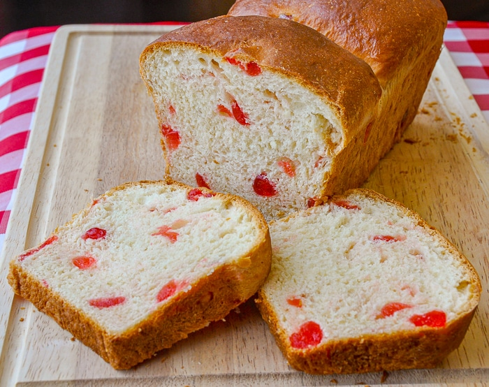 Cherry Bread being sliced on a wooden cutting board