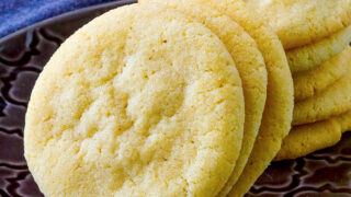 Soft and Chewy Sugar Cookies stacked on a grey patterned plate with a glass of milk in the background