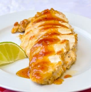 Glazed Lime Apricot Chicken Breasts on a white plate with lime garnish