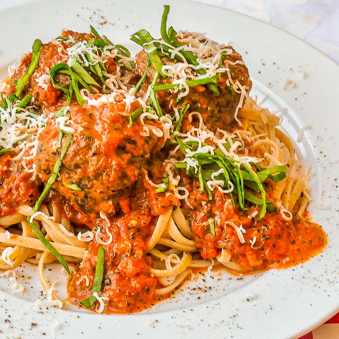 Linguine with Meatballs in Blush Asiago Sauce shown on a white plate with basil and grated cheese garnish