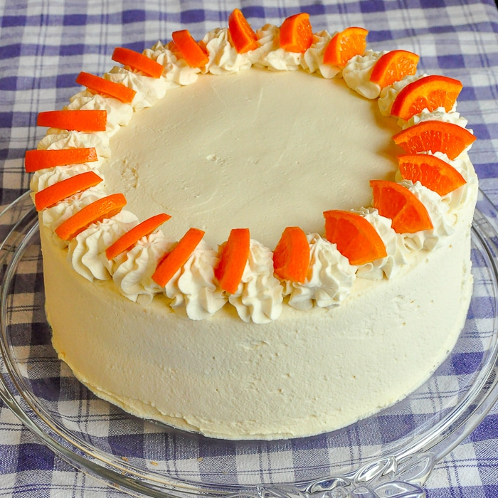 Orange Creamsicle Cake photo of entire completed cake on a clear glass cake plate