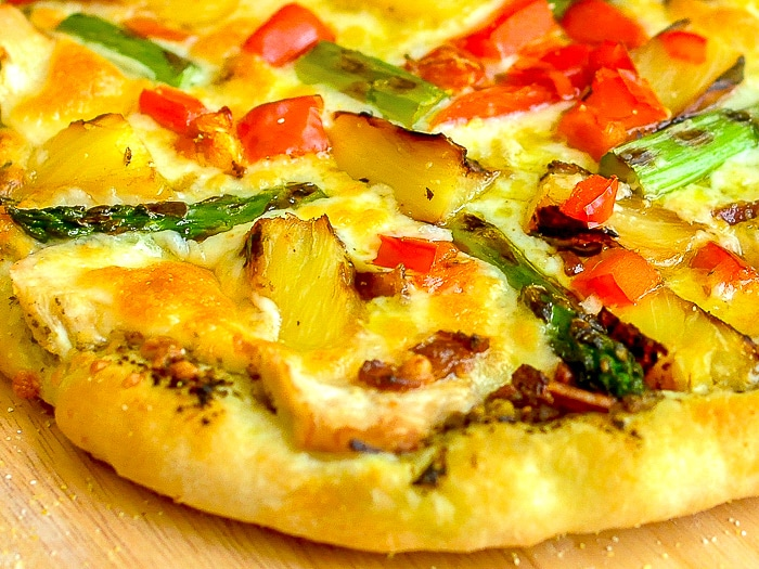 Pineapple Pizza with Grilled Chicken and Asparagus close up photo of cooked pizza