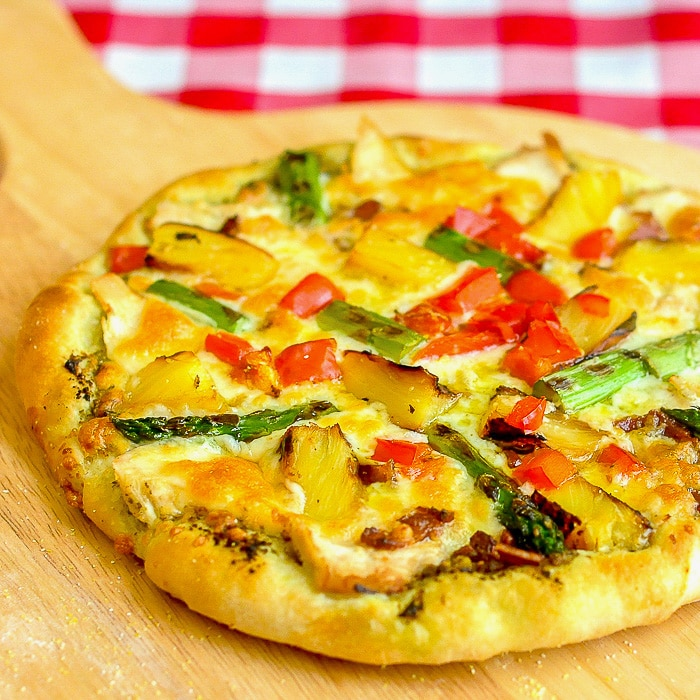 Pineapple Pizza with Grilled Chicken and Asparagus shown on a wooden peel