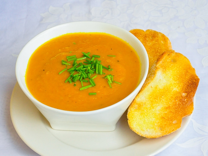 Roasted Carrot Celeriac Soup in a white bowl with garlic toast on the side