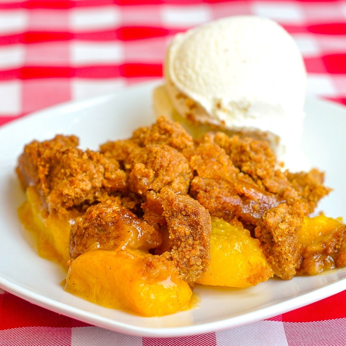 Ginger Snap Peach Crumble photo of a singoe serving on a white plate with vanilla ice cream