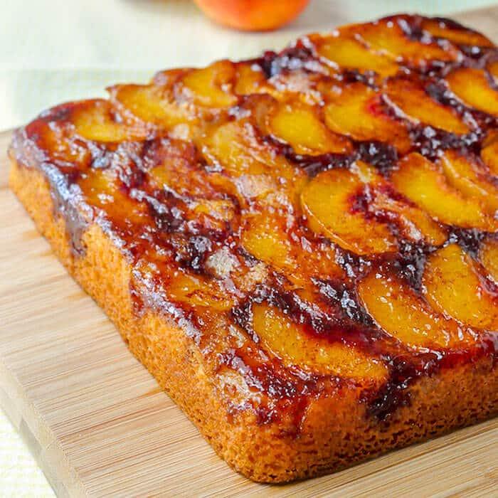 Peach Upside Down Cake uncut on a wooden board