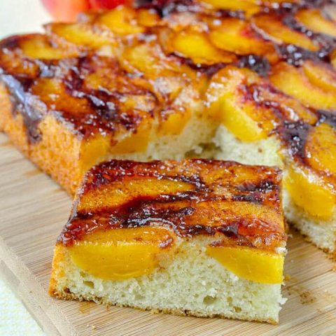 Peach Upside Down Cake close up photo of a single sice on a wooden cutting board.