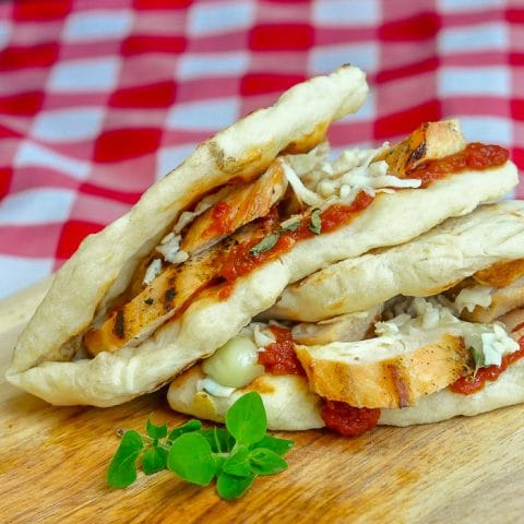 Grilled Chicken Parmesan Flatbread Sandwiches close up photo on wooden cutting board