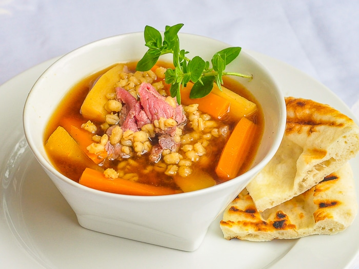 Steak and Barley Soup shown with flatbread on the side