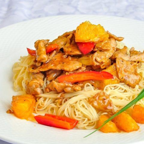 Spicy Honey Orange Sliced Pork close up photo of single serving on white plate