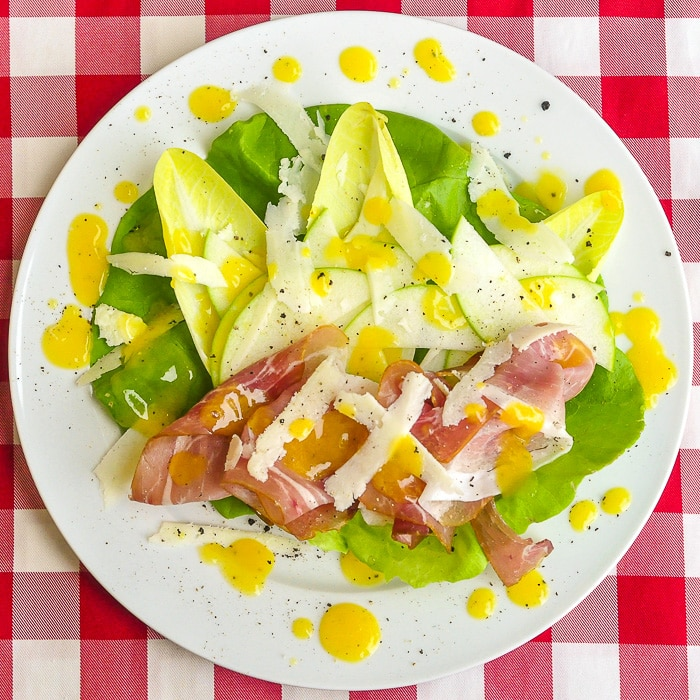 Mango Orange Dressing on Prosciutto Apple Salad on a white plate on a red checkered background