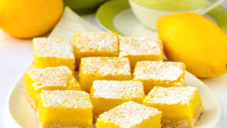 Lemon bars on a white platter with tea service in the background