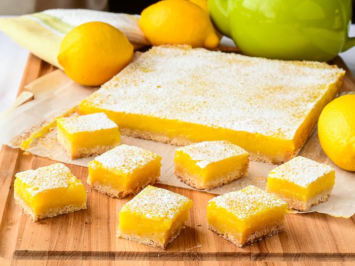 Lemon bars shown with fresh lemons