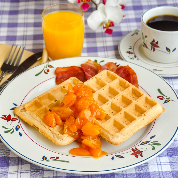 Cinnamon Waffles with Apricot Orange and Brandy Compote shown on flower pattern plate with orange juice and coffee in background