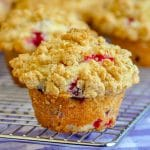Cranberry Crunch Muffins. single muffin with muffins on cooling rack in background.