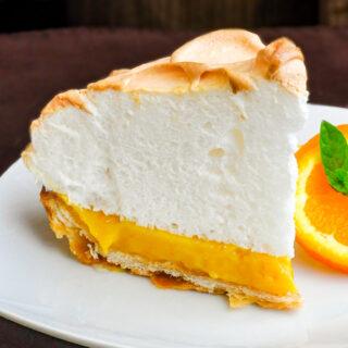 Orange Curd Meringue Tart photo of a single slice on a white plate with orange slice and mint garnish