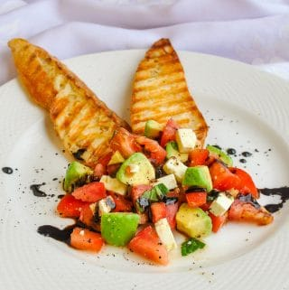 Tomato Avocado Feta Crostini single serving on white plate