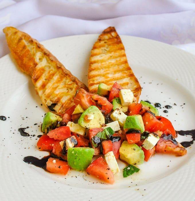 Tomato Avocado Feta Crostini single serving on white plate