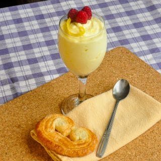 Easy Lemon Mousse in a wine glass with a palmier cookie, napkin and spoon at the base