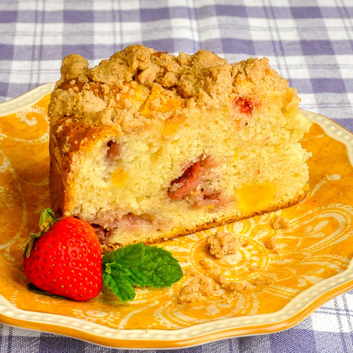 Strawberry Mango Crumb Cake close up photo of single slice on a yellow patterned plate