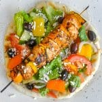 Chicken Souvlaki with Lemon Mint Tzatziki close up image with Greek Salad on a flatbread