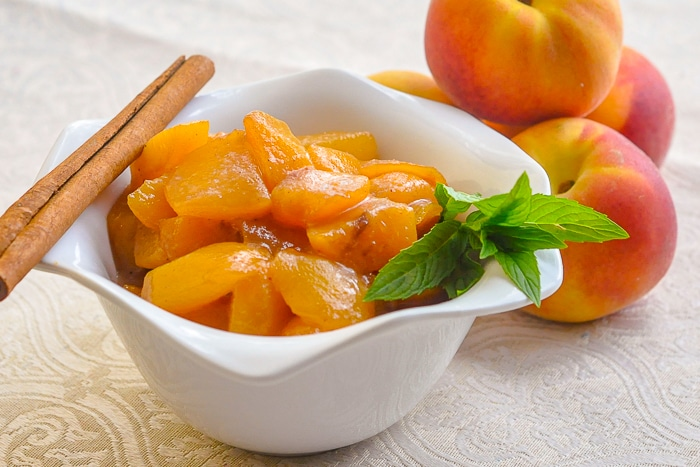 Honey Peach Compote in a white bowl with fresh peaches in background