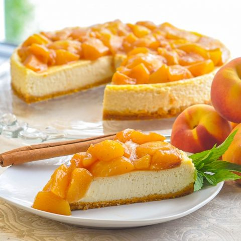 Peaches and Cream Flan photo of a single slice on a white plate with peaches on the side