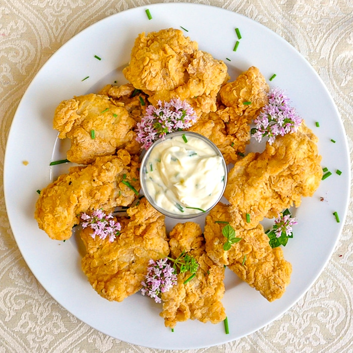 Chicken Fried Fish Nuggets on a white plate with chive flowers
