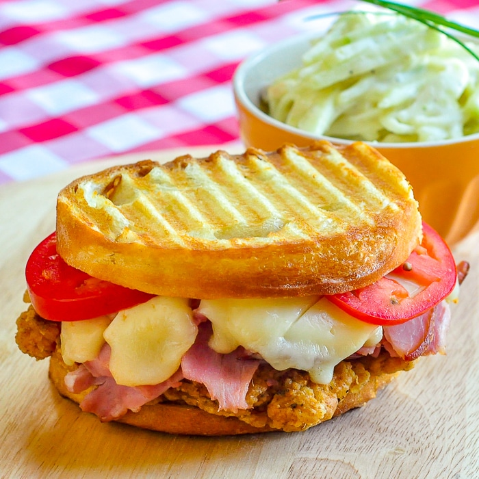 Fried Chicken Club Sandwich Panini pn a wooden cutting board with coleslaw in background