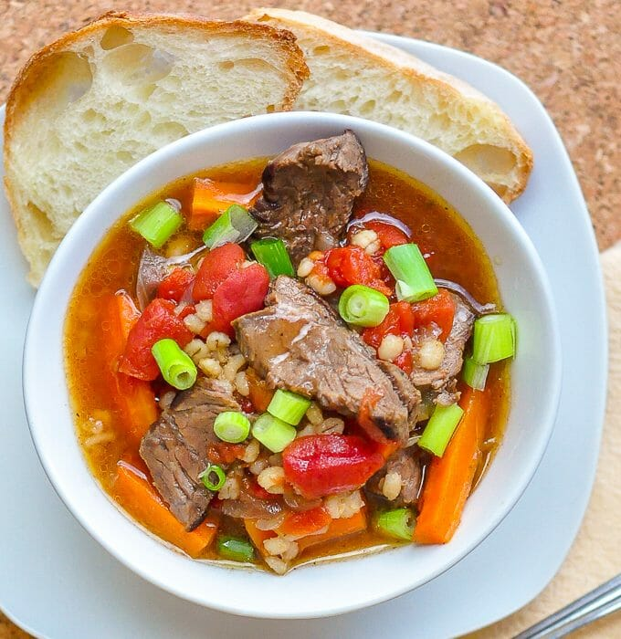Steak Tomato and Smoked Paprika Soup shown in a white bowl with artisan bread on the side