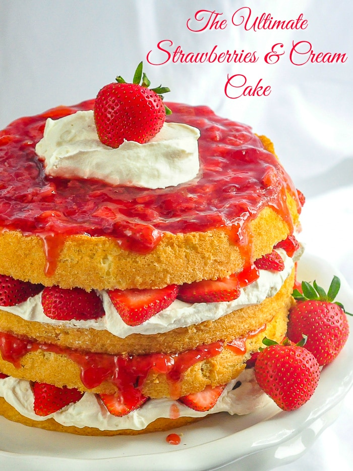 The Ultimate Strawberries and Cream Cake photo of cake on a white pedestal stand with title text added for Pinterest