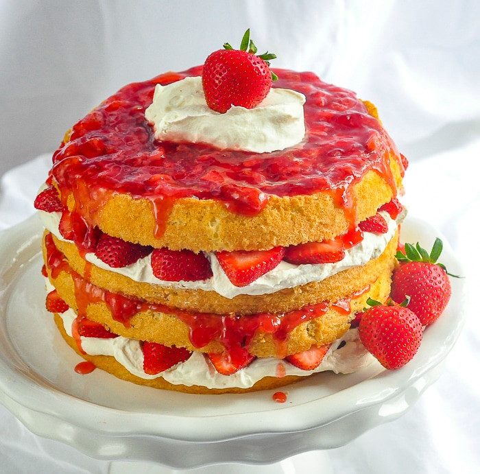 The Ultimate Strawberries and Cream Cake photo of entire finished cake on a white cake pedestal