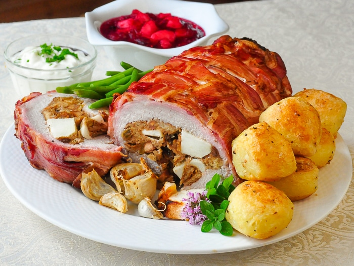Apple Almond Stuffed Pork Loin in a Bacon Blanket photo of sliced roast with garlic and roasted potatoes on a white platter