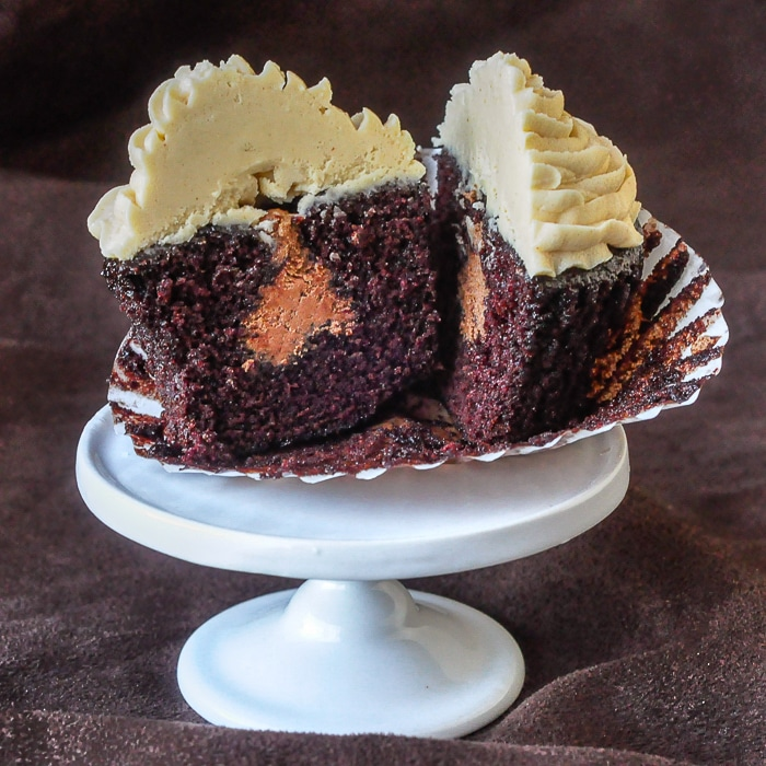 Inside Out Peanut Butter Cup Cupcakes photo of one cupcake cut open to reveal the chocolate frosting filling
