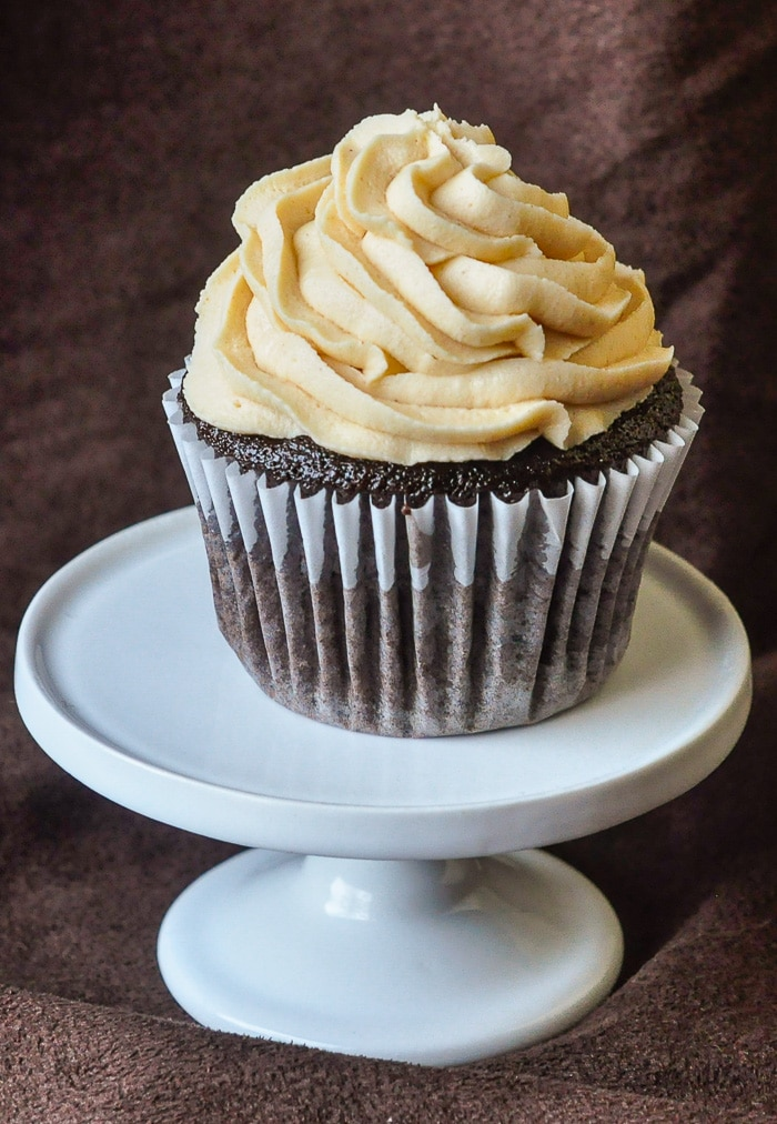 Inside Out Peanut Butter Cup Cupcakes photo of single white cupcake on a white cupcake pedestal stand
