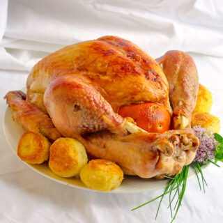 Orange Clove Brined Roast Turkey with roasted potatoes and herbs on a white platter