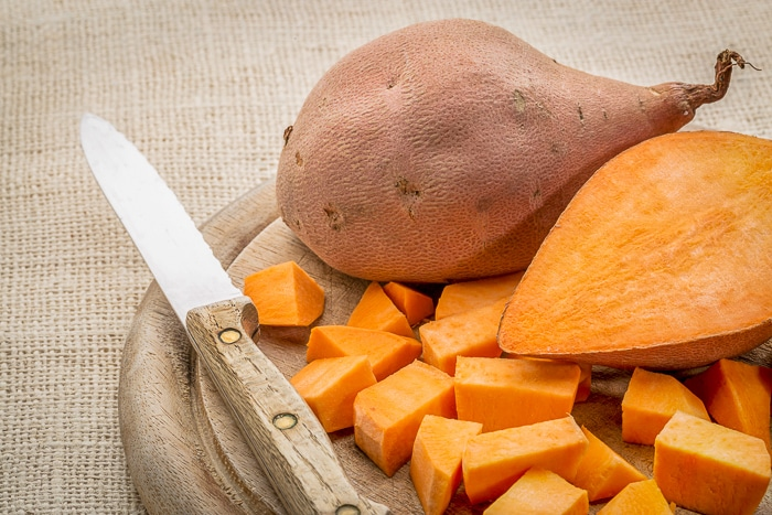 Sweet potato cut and diced on a cutting board. Stock photo