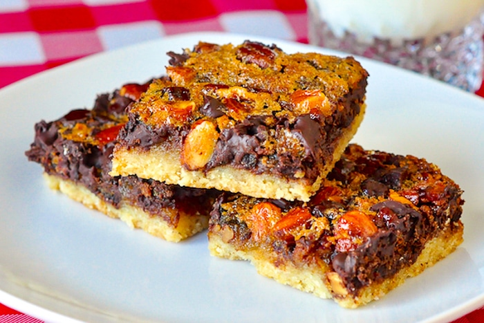Chewy Chocolate Pecan Almond Bars stacked on a white serving plate