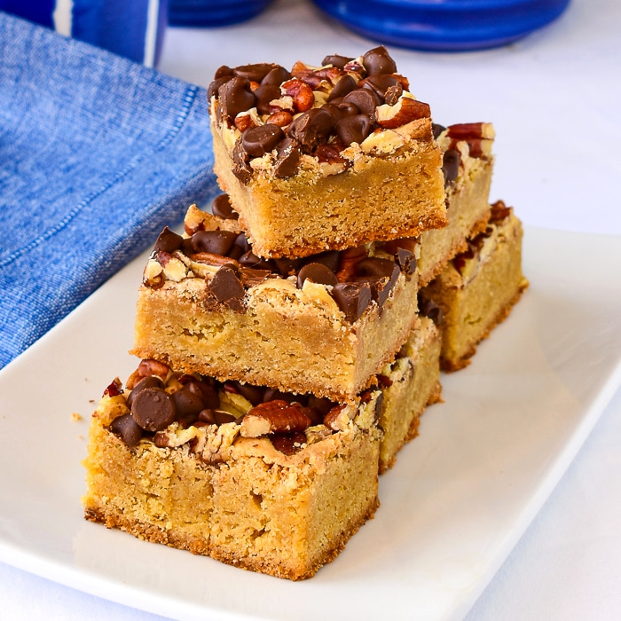 Chocolate Pecan Blondies stscked on a white serving platter