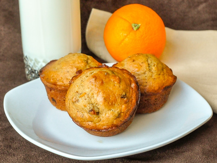 Orange Date Muffins wide shot of 3 muffins on a serving plate with glass of milk and an orange in background