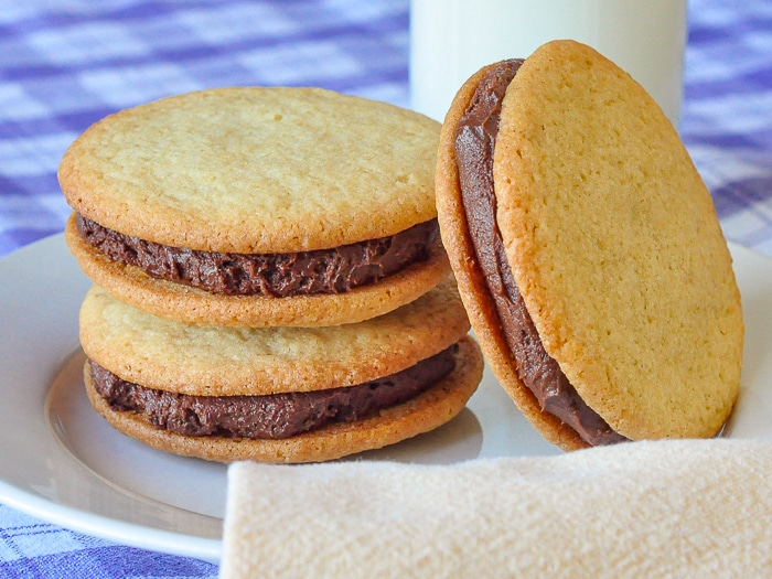 Vanilla Fudge Sandwich Cookies on a white plate with a glass of milk in background