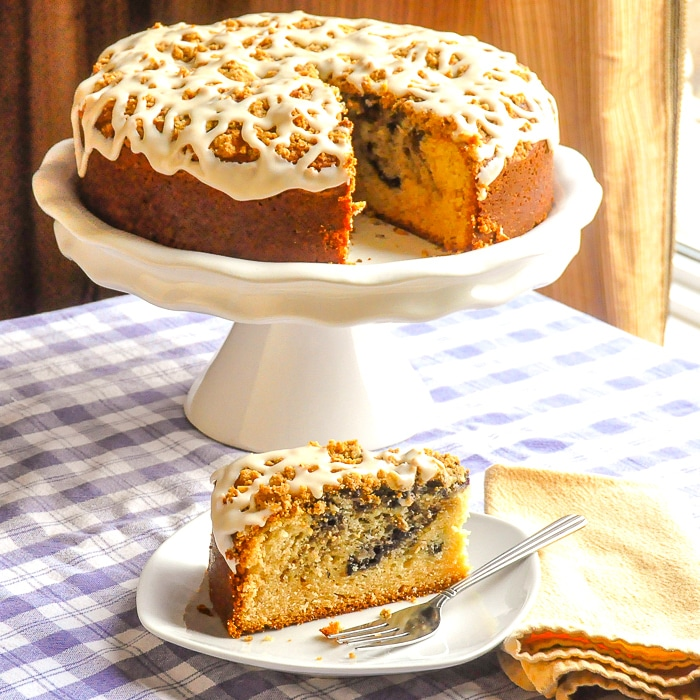 Blueberry Swirl Coffee Cake photo od entire cake on a white pedestal with one slice cut out