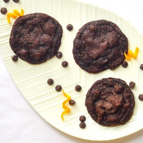 Orange Dark Chocolate Chip Cookies close up overhead phhoto of cookies with orange zest on a white leaf shaped platter.