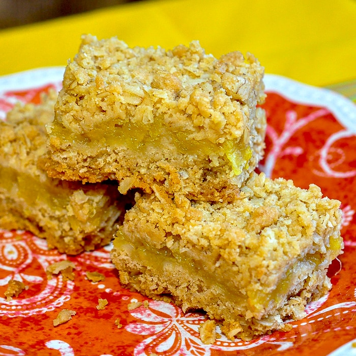 Pineapple Oat Bars photo of 3 cookie squares on an orange plate.