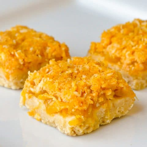 Orange Pineapple Crumble Bars close up featured image of cookies on a white plate