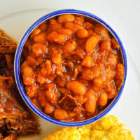 Close up photo of Maple Chipotle Baked Beans in a white ramekin with blue accent
