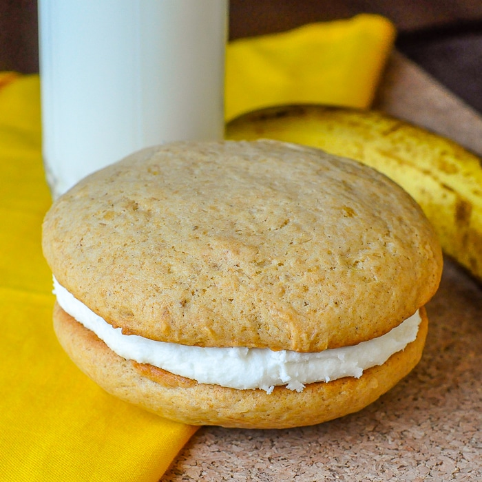 Banana Cream Cheese Whoopie Pies close up photo of a single whoopie pie with milk and banana in background